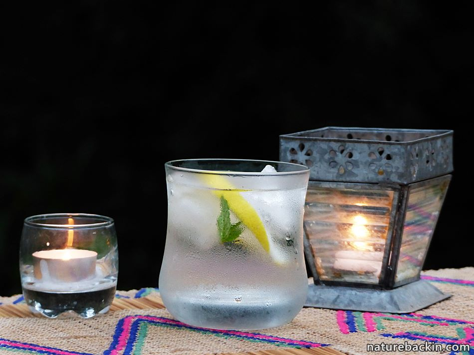Ice-cold sundowner with lemon and mint and candles in suburban garden
