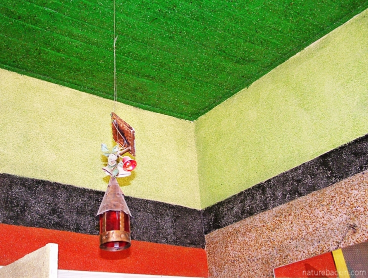 Painted ceiling and walls encrusted with glass, and decorated lamp, Owl House, South Africa